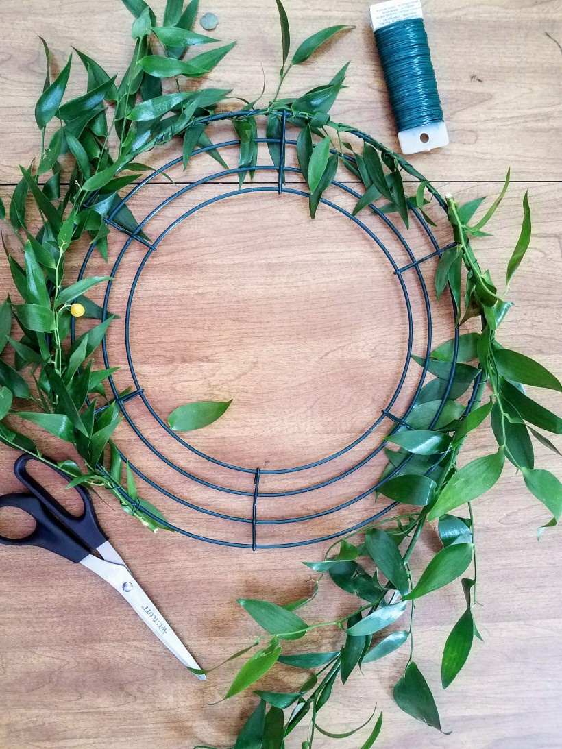 Start of a fresh mixed greens wreath. Fresh stems are surrounding the outside of the wreath frame. Scissors and floral wire are in the picture.