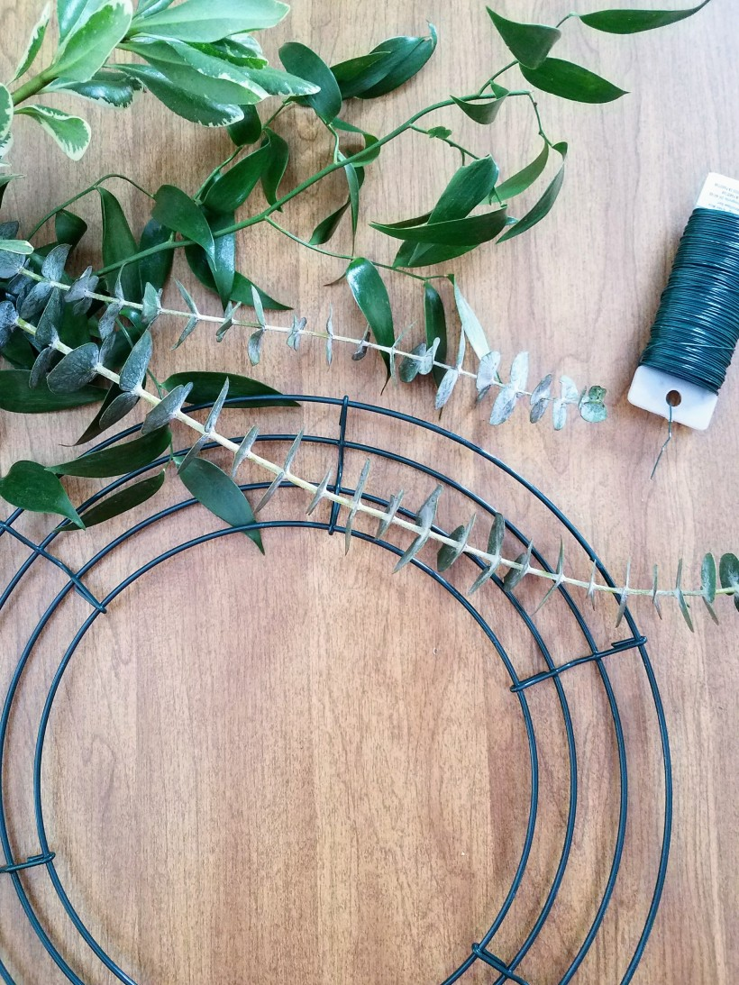 Materials needed to make a mixed greens wreath including a wreath frame, floral wire, scissors and fresh stems