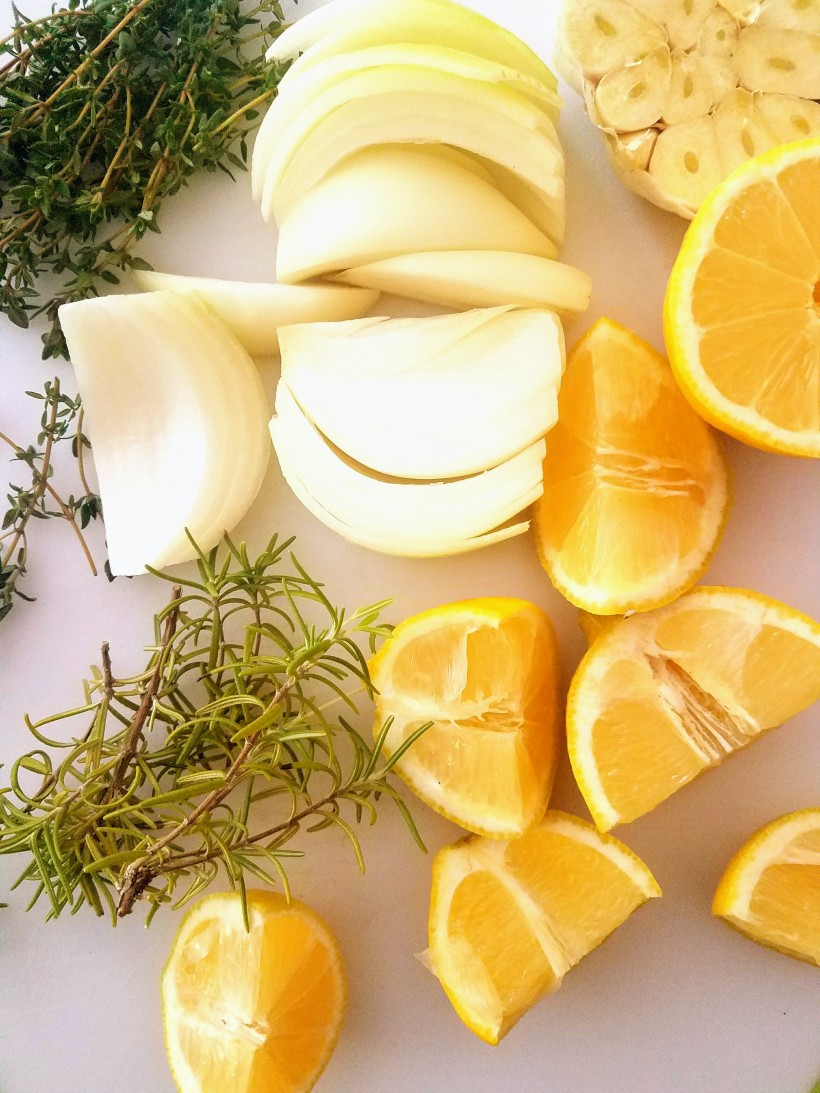 Cutting board with onions, lemons, garlic and fresh herbs