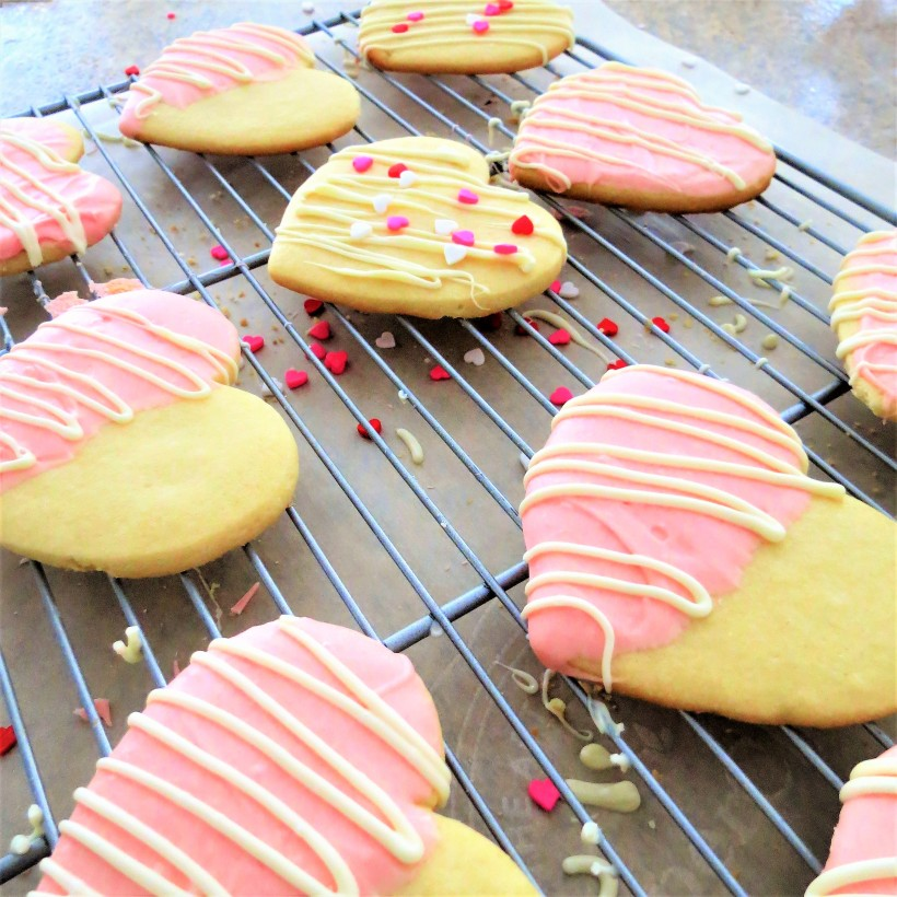 Heart shaped sugar cookies decorated with white chocolate and heart shaped sprinkles