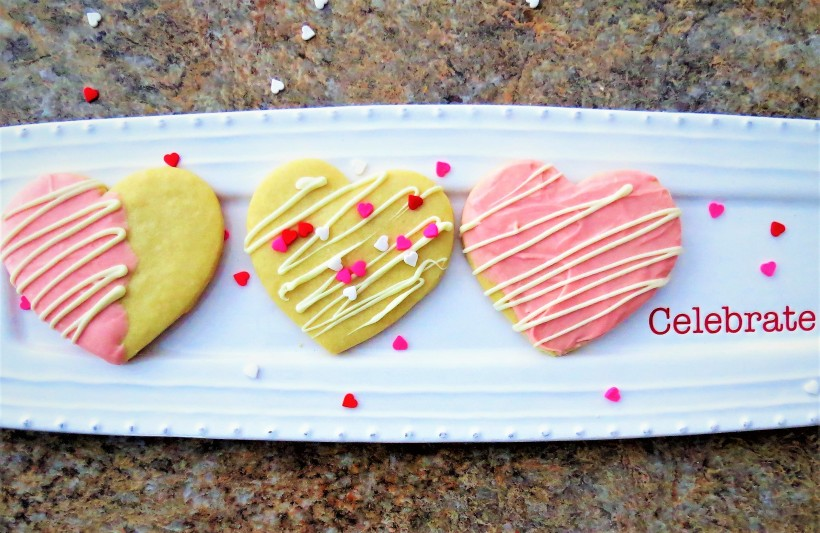 Heart shaped sugar cookies on a white plate decorated with pink icing and heart shaped sprinkles