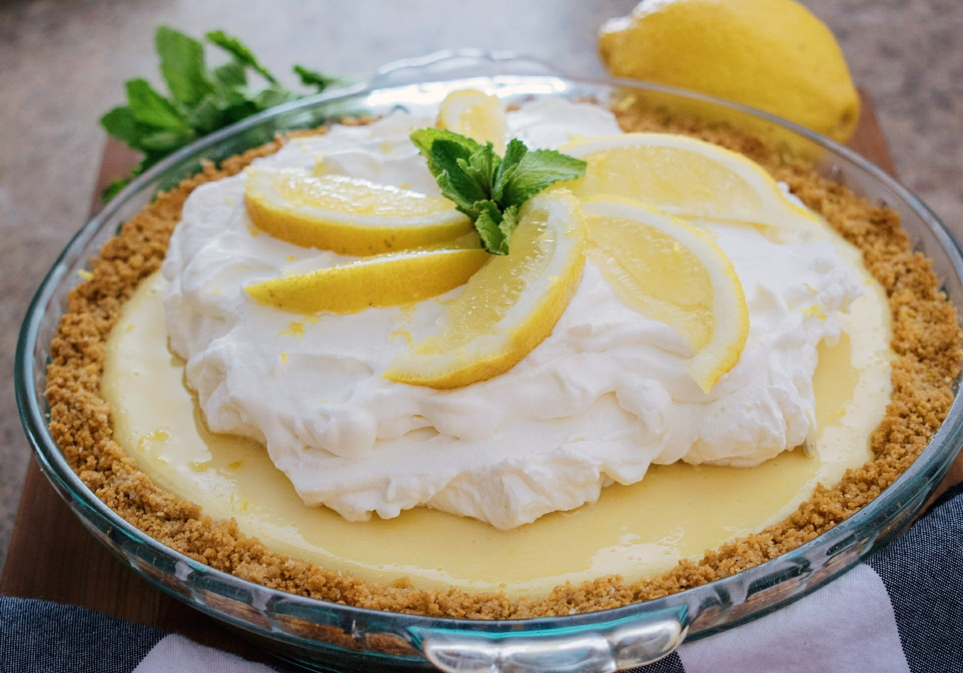 Lemon pie with graham cracker crust, whip cream topping, sliced lemon wedges and mint leaves as garnish