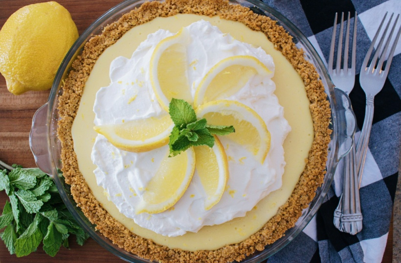Lemon Pie with graham cracker crust, whip cream topping, lemon wedges and mint as garnish