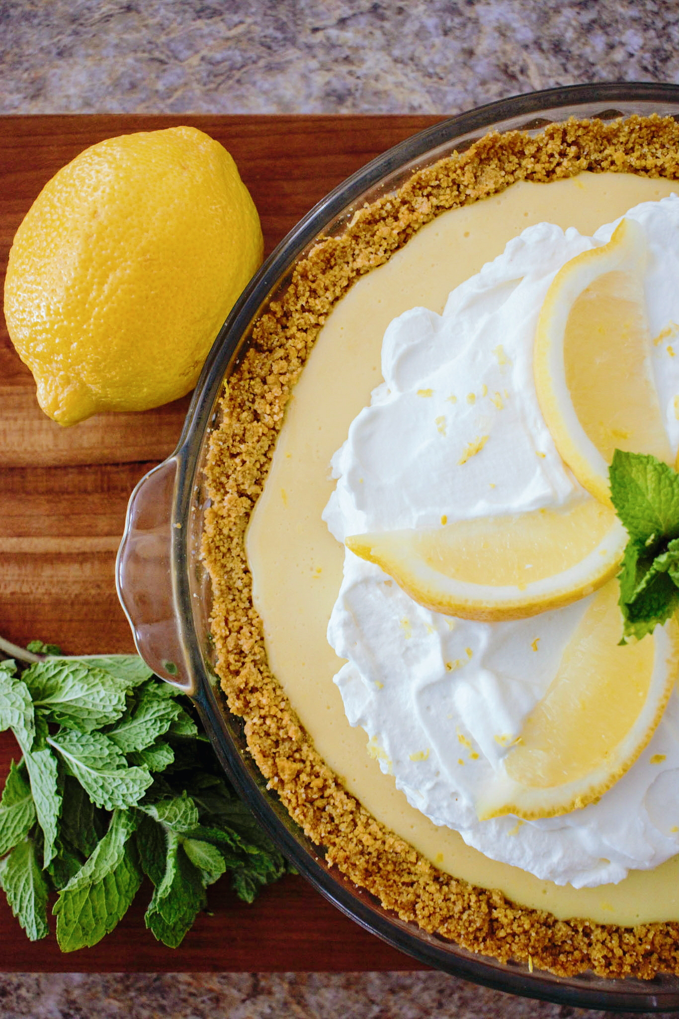 Lemon Pie with graham cracker crust, whip cream topping and sliced lemon wedges and mint leaves for garnish