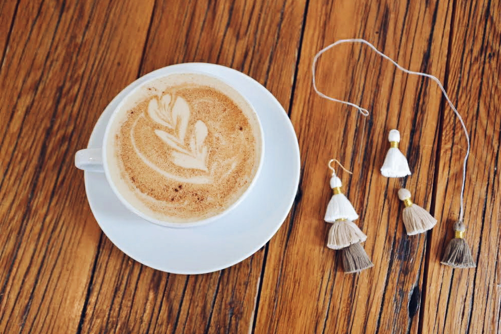 Tassels and a needle and thread on a wood table next to chai tea in a white ceramic coffee cup