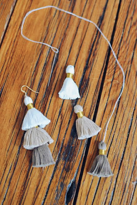 Tassels and a needle and thread on a wooden table