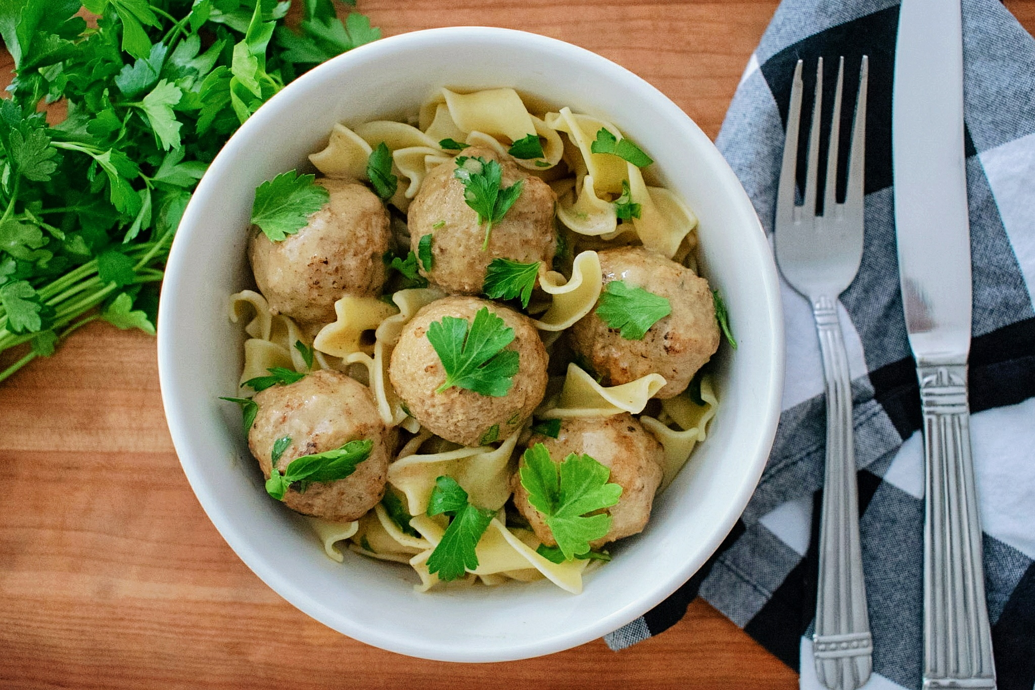 Egg noodles topped with swedish meatballs and a sprinkle of fresh parsley
