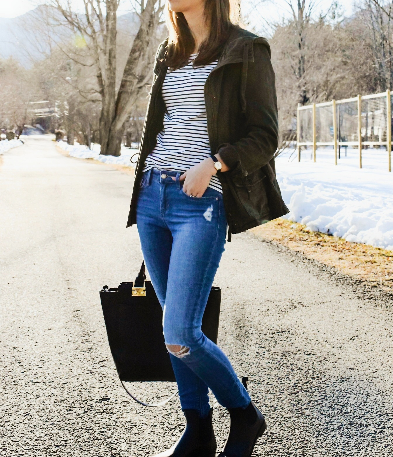 Wearing a green military jacket, striped shirt, distressed denim, Sam Edelman rain boots, and black tote