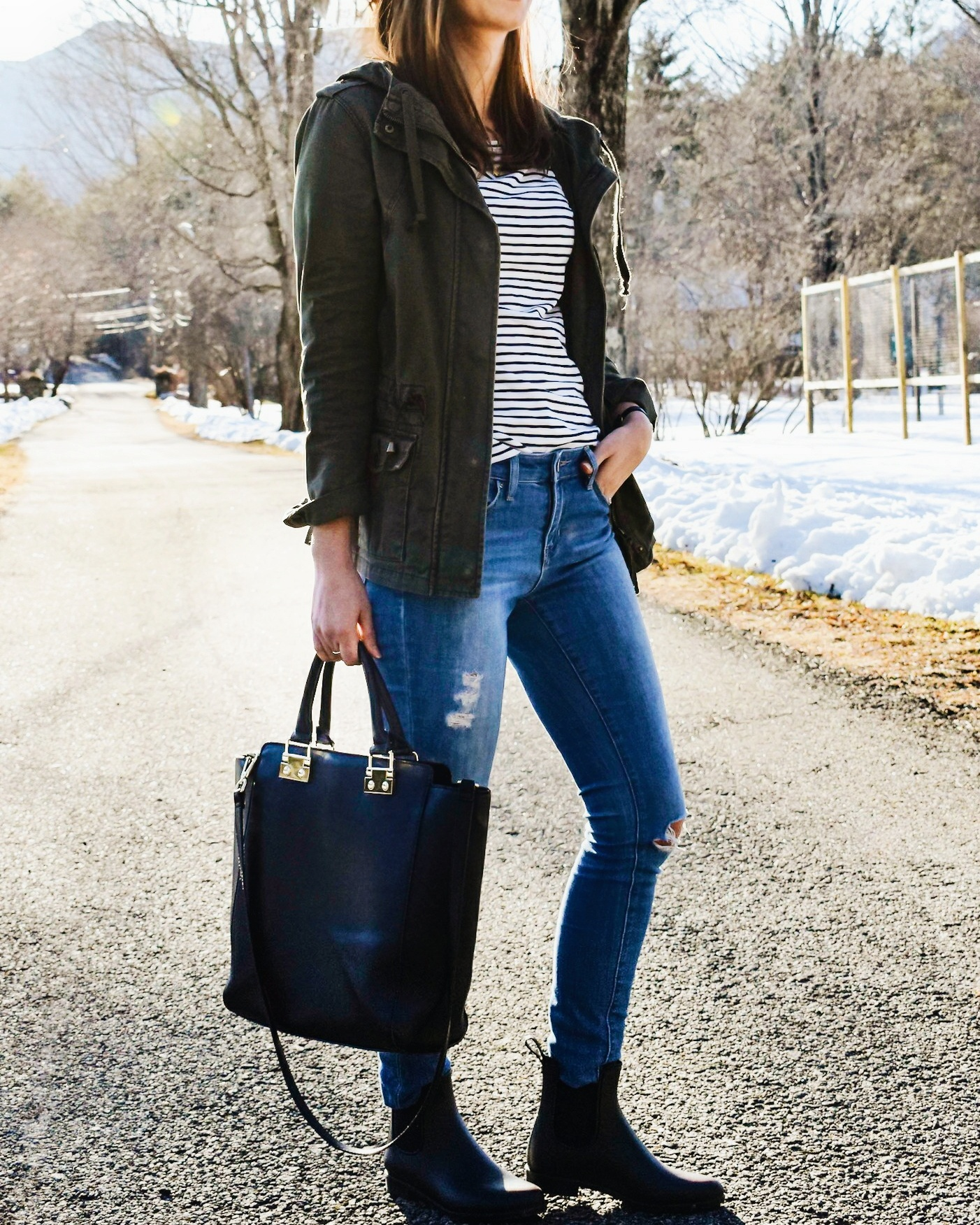 Wearing a green military jacket, striped shirt, distressed denim, Sam Edelman rain boots, black tote bag