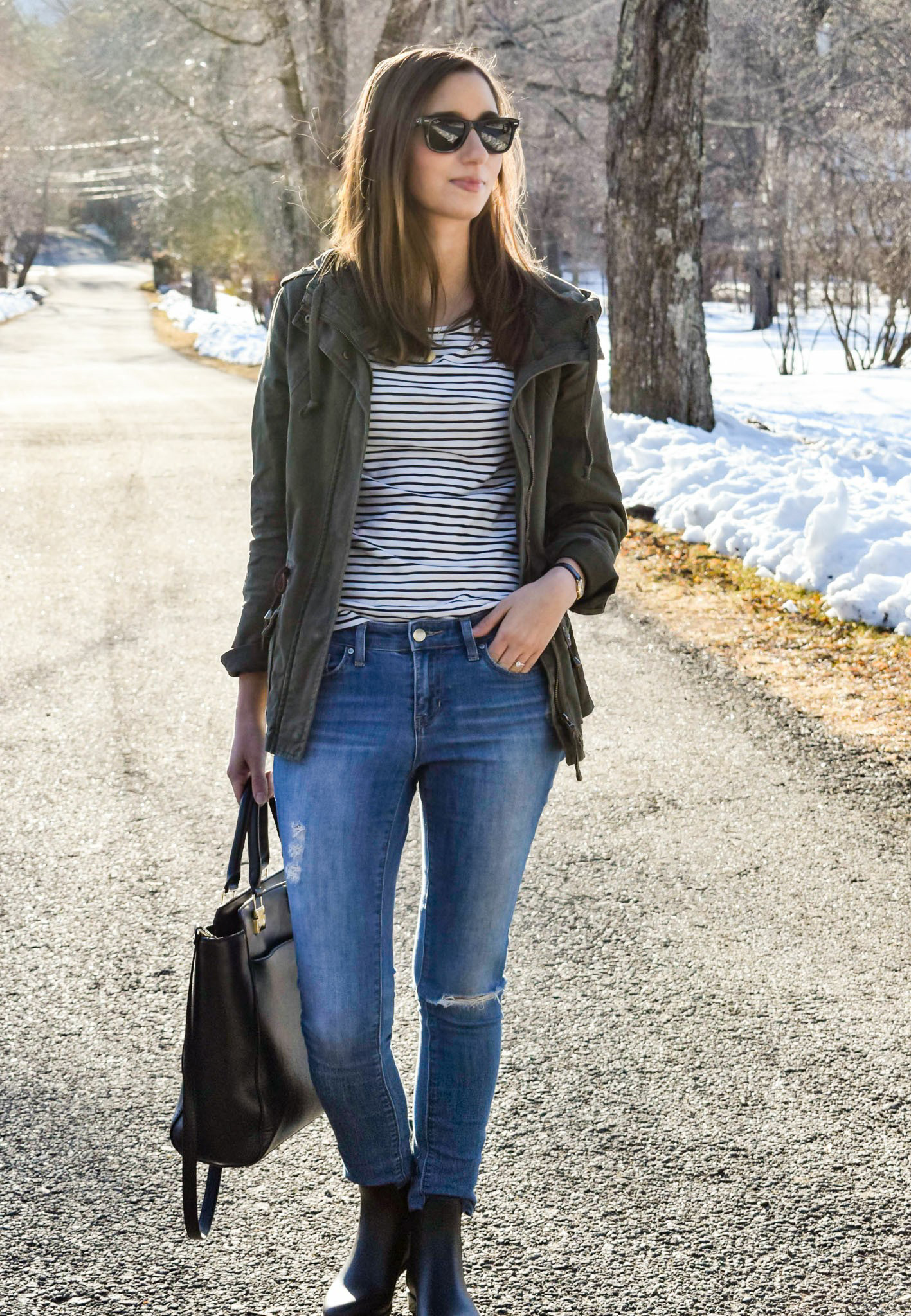 Wearing a military green jacket, striped shirt, distressed denim, black tote bag and black Sam Edelman rain boots