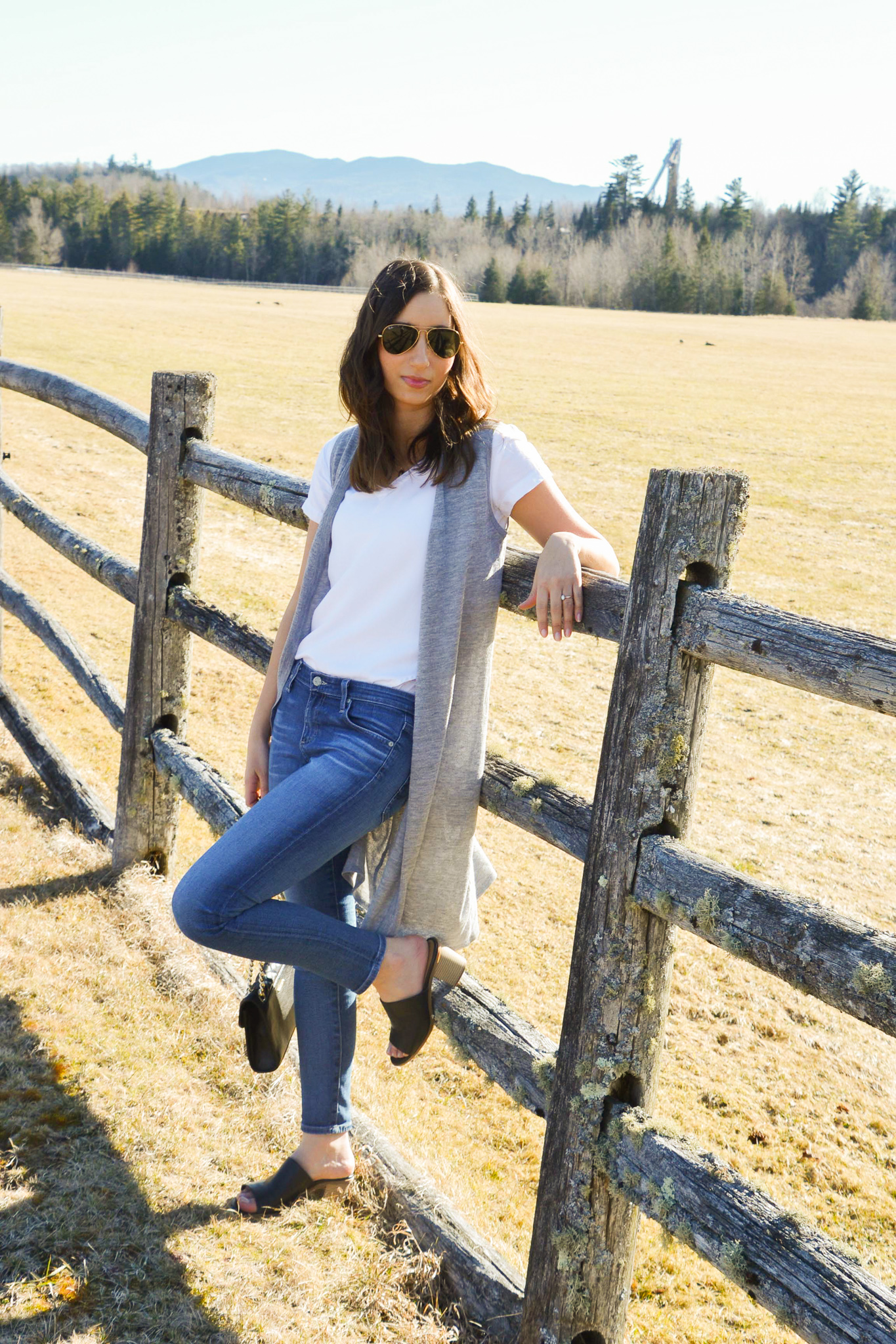 Leaning against a fence wearing medium wash jeans, black mules, white t-shirt and a grey duster