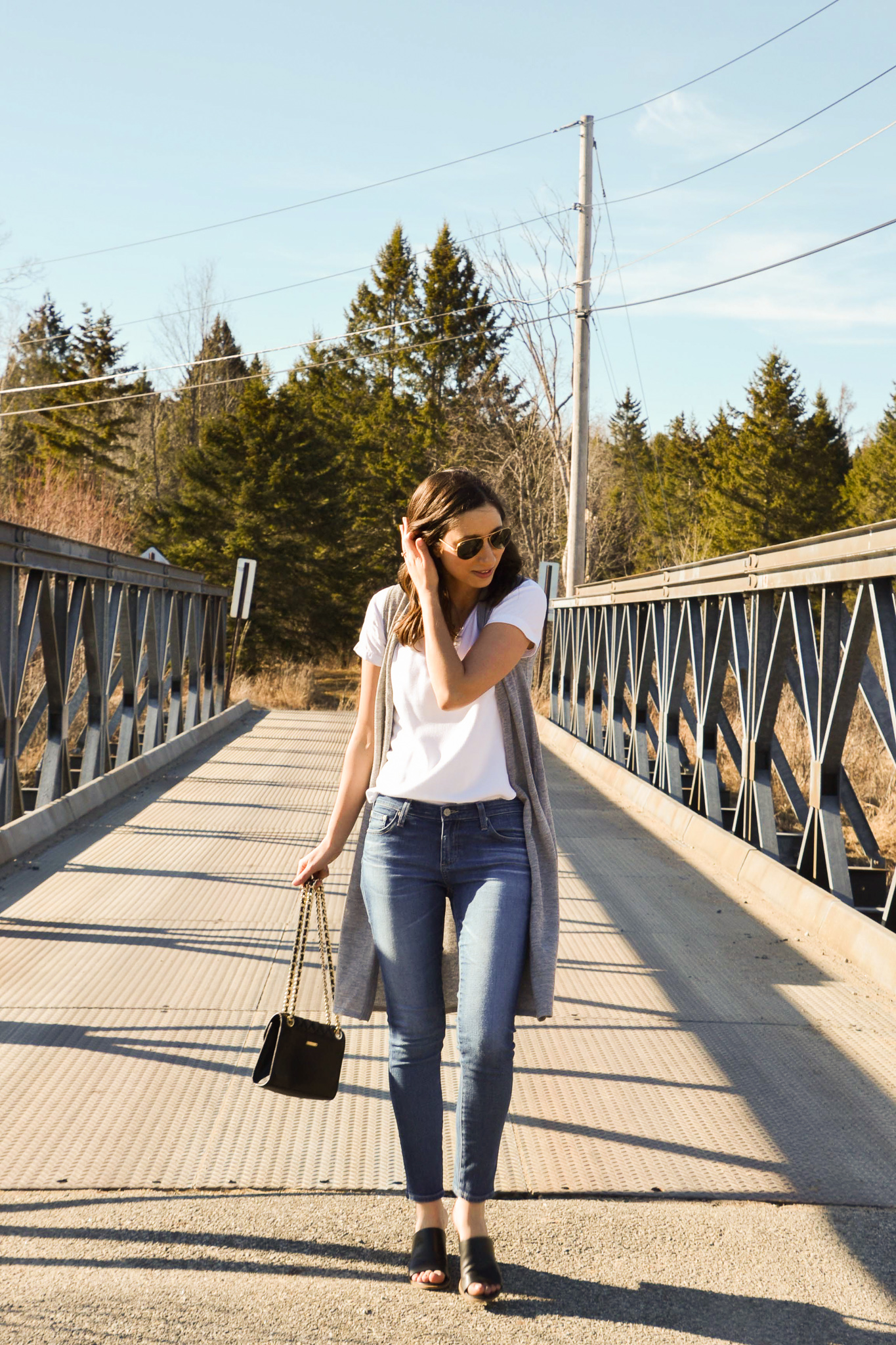 Walking on a bridge wearing medium wash denim, black mules, white shirt and a grey duster