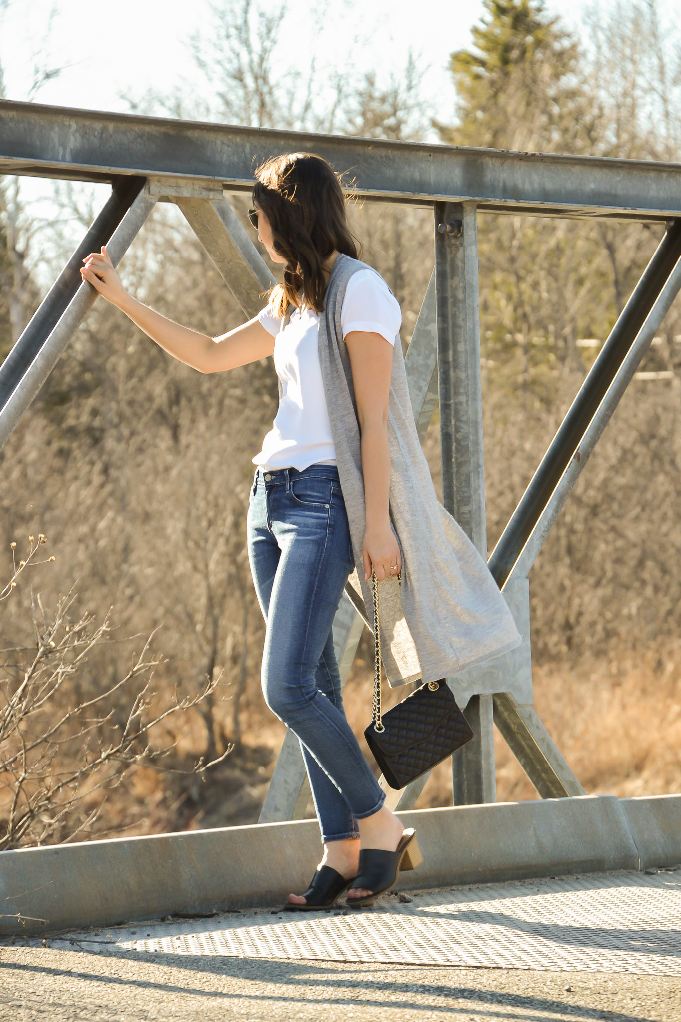 On a bridge wearing medium wash jeans, white shirt, black mules and a grey duster
