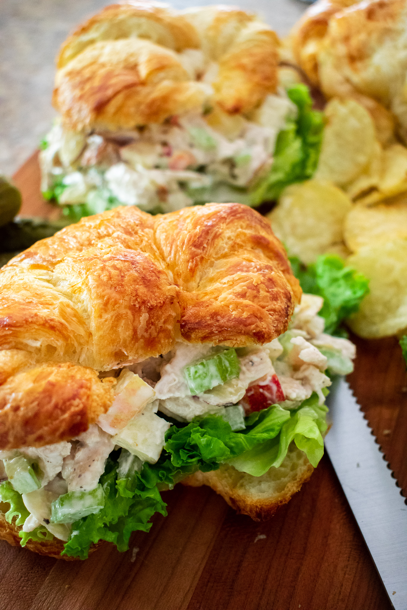 Chicken salad piled high on a flaky croissant surrounded by potato chips and dill pickles