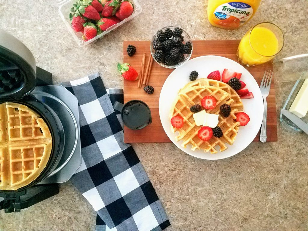 Waffles From Scratch on a plate with fresh fruit, real maple syrup and orange juice poured in a glass.