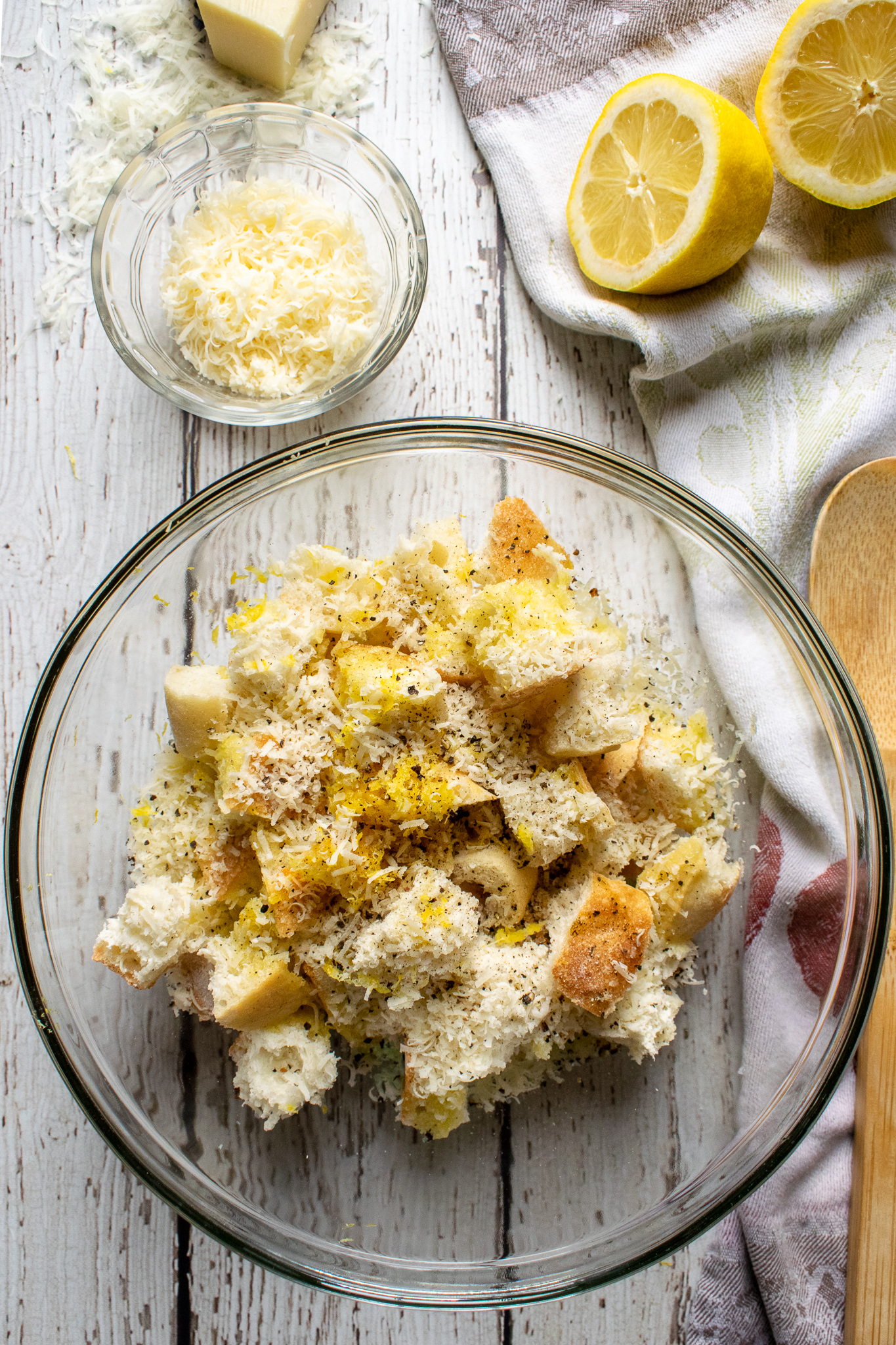 A bowl filled with cubed ciabatta bread, lemon zest, minced garlic, grated parmesan, olive oil, salt and pepper. Lemon slices and grated Parmesan cheese are next to the bowl.