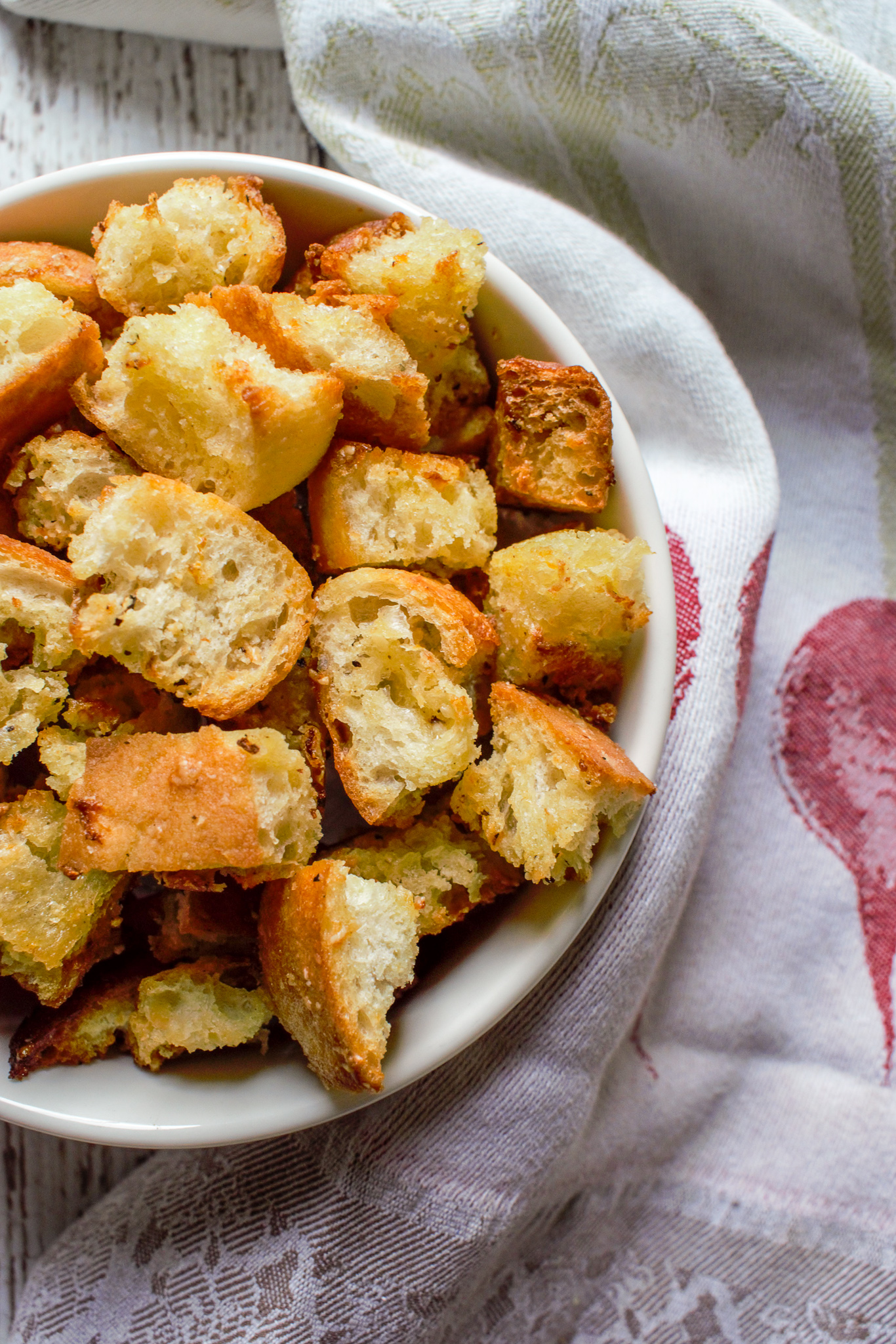 Parmesan and Garlic Croutons in a round, white bowl next to a kitchen linen.