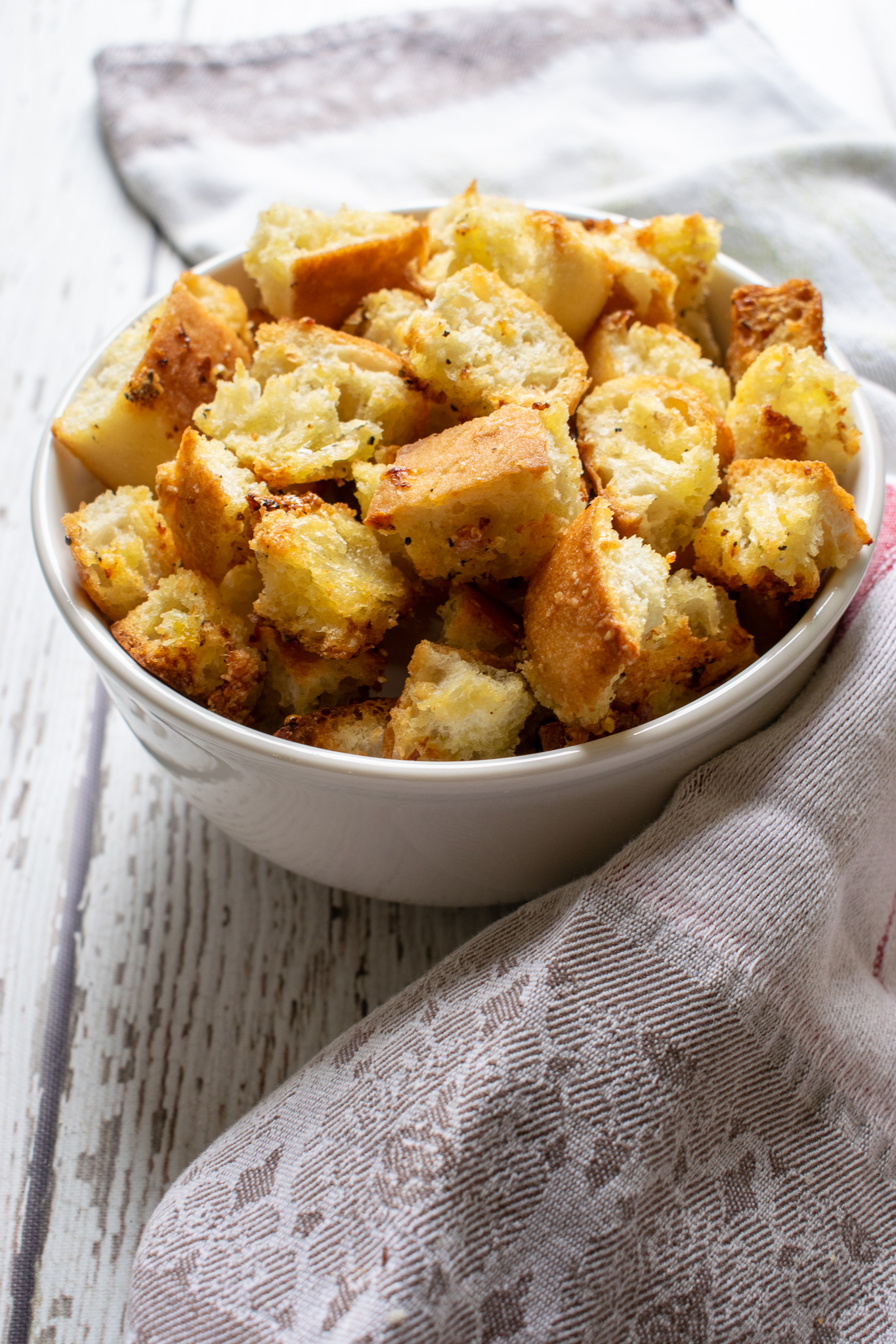 Parmesan and Garlic Croutons in a bowl next to a linen towel.