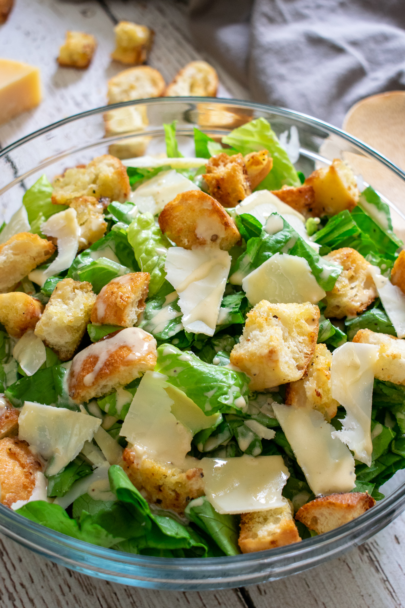 Crisp romaine lettuce chopped up in a bowl with grated parmesan, parmesan garlic croutons and homemade caesar dressing.