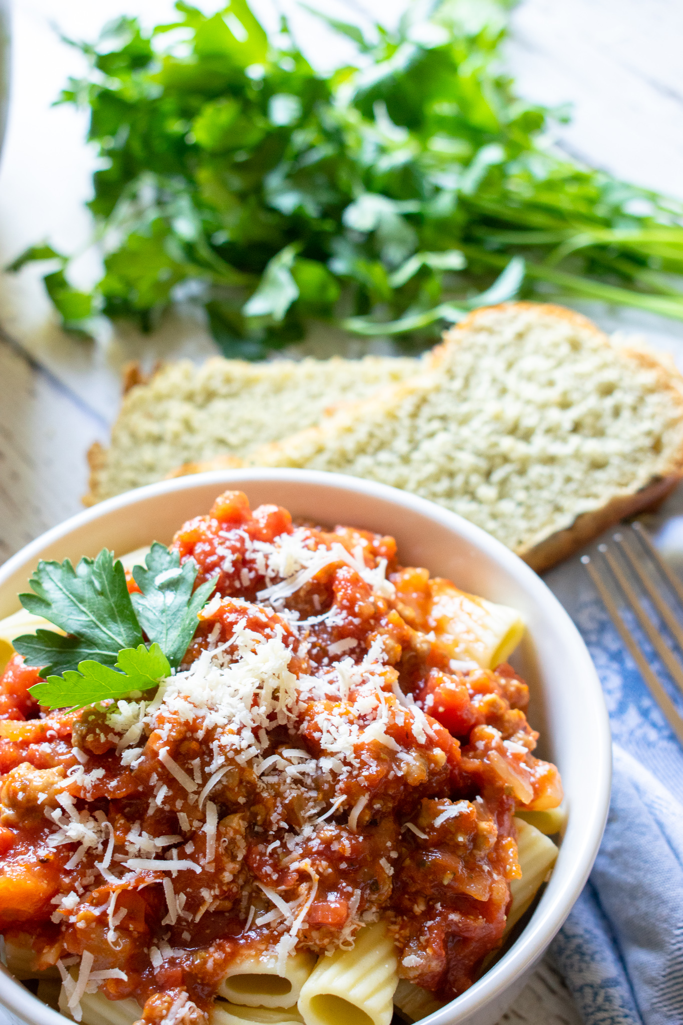Italian Sausage sauce on top of rigatoni pasta garnished with freshly grated parmesan cheese and parsley.